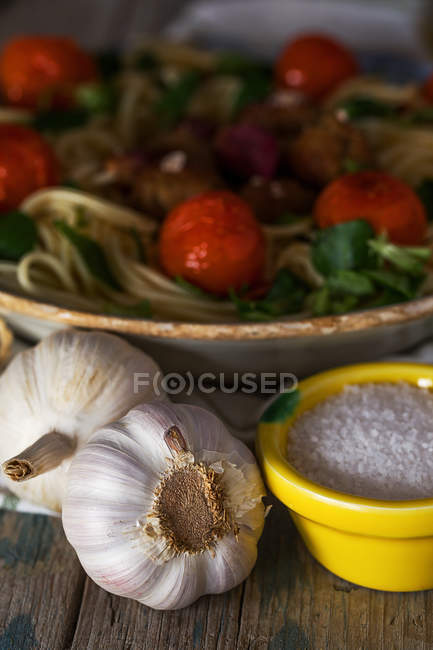 Garlic bulbs and salt in front of spaghetti and meatballs garnished with basil leaves and grilled tomatoes on platter — Stock Photo