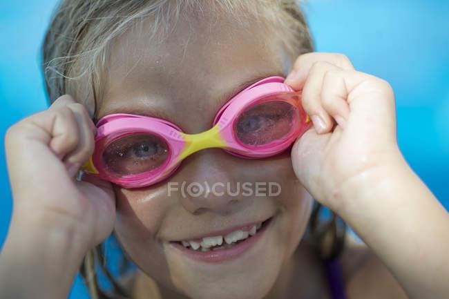 Smiling kid adjusting goggles and looking at camera — Stock Photo