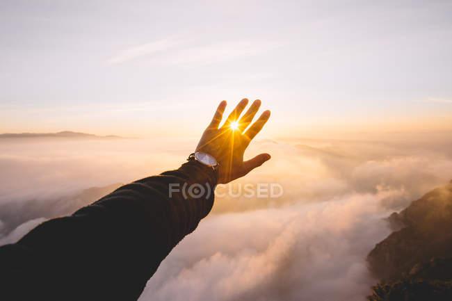 Hand, die Sonne auf Hintergrund Wolken schließen. — Stockfoto