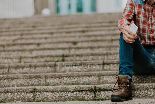 Cropped image homme en vêtements décontractés assis sur les marches de la rue et tenant smartphone dans la main — Photo de stock