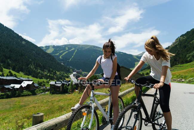 Les filles en vélo dans la campagne de montagne — Photo de stock