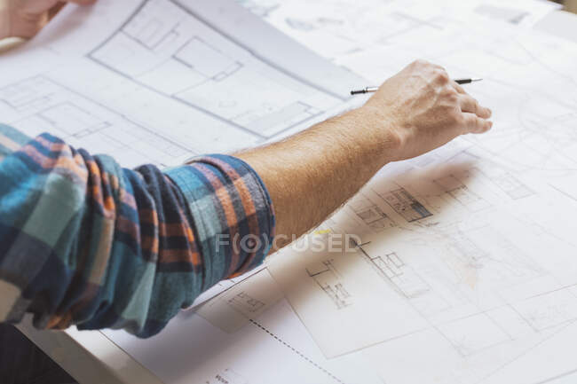 Cropped view of male hand working with blueprints — Stock Photo
