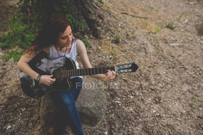 High angle portrait of smiling red haired girl sitting on rock and playing guitar — Stock Photo
