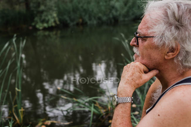 Side view of  senior man in glasses looking away with hand on chin against of countryside river on background — Stock Photo