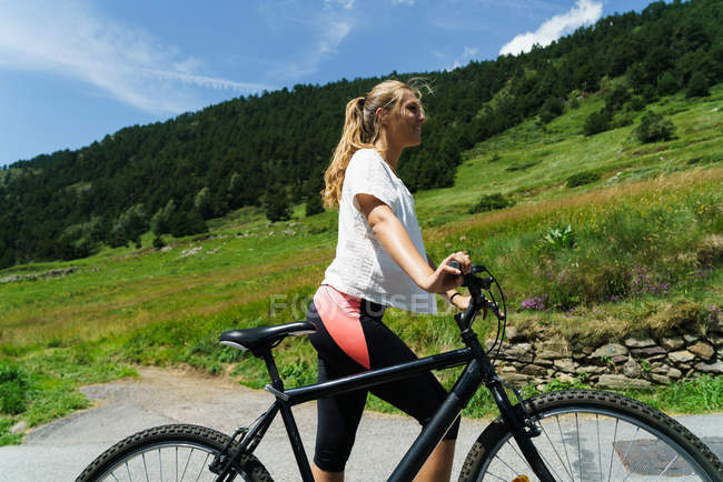 Girl walking with bicycle on mountain countryside road — Stock Photo
