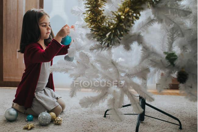 Vista laterale della ragazza adorabile che si siede sulle ginocchia e commercializzazione Bagattelle bianco albero di Natale decorativo in camera — Foto stock