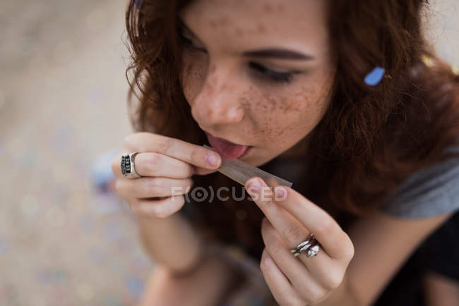 Girl with freckles rolling joint — Stock Photo