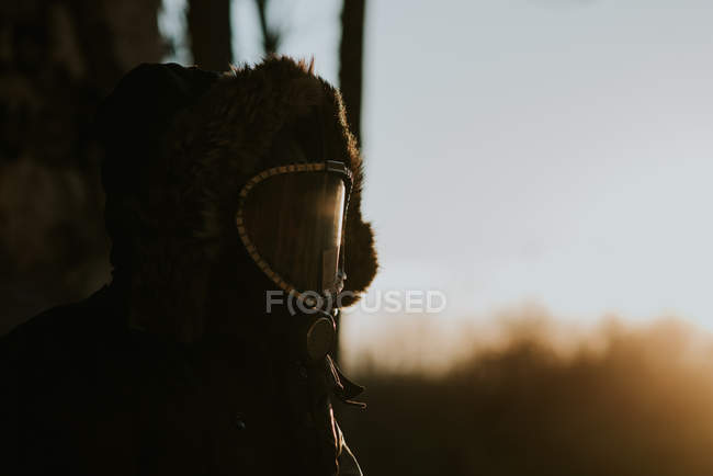 Portrait of man wearing coat hood and gas mask at countryside scene — Stock Photo