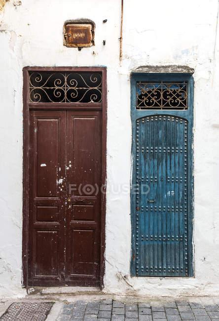 Vista esterna della facciata bianca con due porte shabby — Foto stock