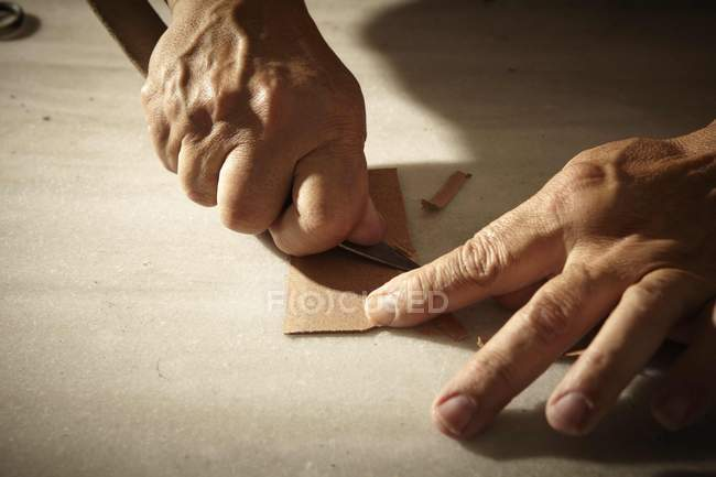 Artisan working with leather and tools — Stock Photo