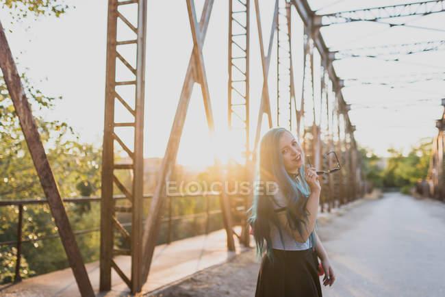 Дівчина з блакитним волоссям проведення сонцезахисні окуляри і дивлячись на камеру — стокове фото