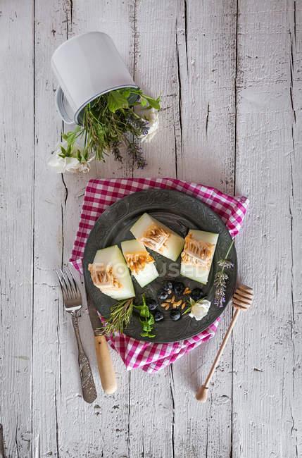 Direttamente sopra vista deliziosa melone e Coppa con fiori sul tavolo rurale — Foto stock