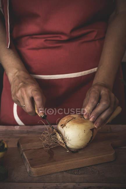 Sezione centrale della donna affettare cipolla su tavola di legno — Foto stock