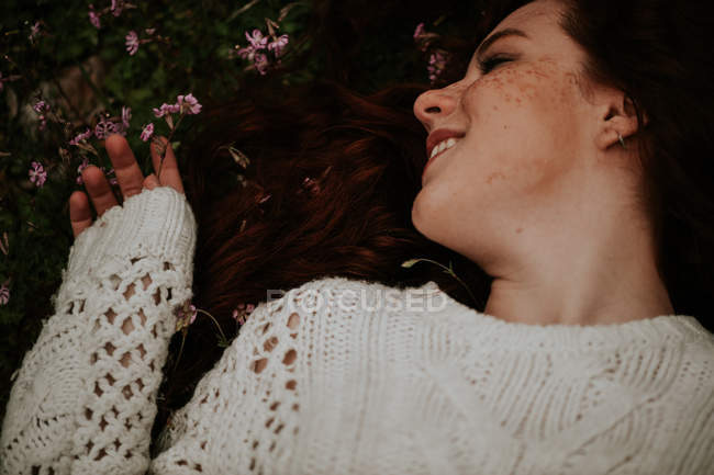 Ginger girl lying on ground and touching blooming flowers — Stock Photo