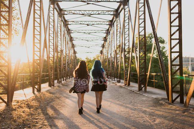 Two girls walking away on bridge. — Stock Photo