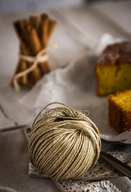 Vista de cerca de madeja de hilo rural en la mesa con torta y palitos de canela - foto de stock