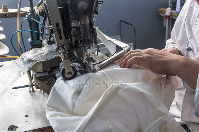 Crop worker sewing on machinery at clothes plant — Stock Photo