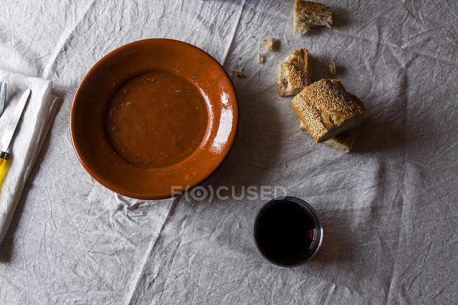 Top view of table with rural bread slices, glass of juice and rural plate on rumpled white tablecloth — Stock Photo