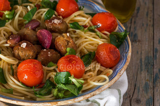 Close up view of pasta with meatballs and cherry tomatoes on plate — Stock Photo