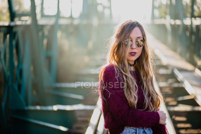 Girl in sunglasses posing on bridge — Stock Photo