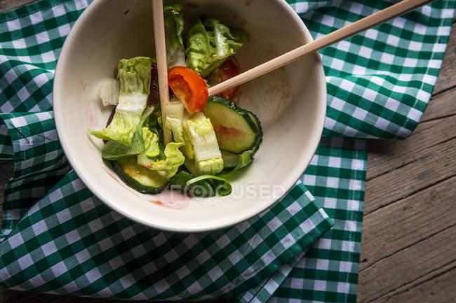 Частково з'їли свіжі овочевий салат в миску з паличками для їжі на тканину на дерев'яні поверхні — стокове фото