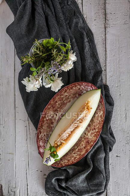 Stillleben von köstlicher Melone und Tasse mit Blumen auf ländlichem Tisch — Stockfoto