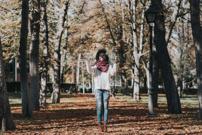 Portrait of happy girl throwing autumn foliage in air at park on sunny day — Stock Photo