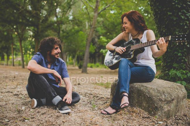 Porträt eines Mannes, der auf dem Boden sitzt und Mädchen mit lockigem rotem Haar zuhört, die auf Stein sitzen und im Wald Gitarre spielen — Stockfoto