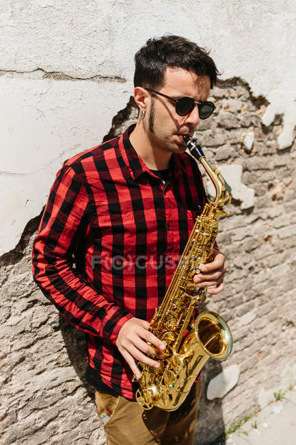 Jazzer lehnt sich an Ziegelwand und spielt auf Saxofon — Stockfoto