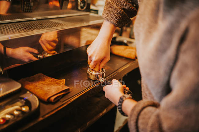 Cropped image of barista pressing coffee in holder with tamper at counter — Stock Photo