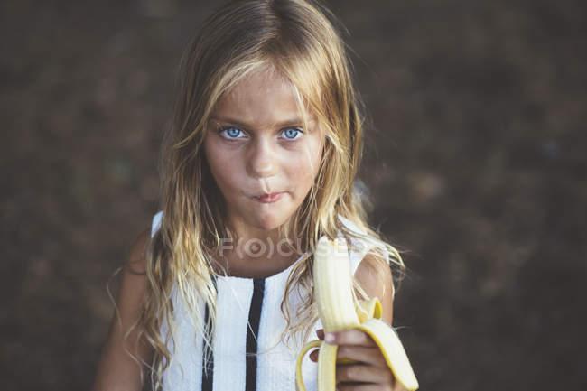 Дівчинка їсть банан і дивлячись на камеру — стокове фото