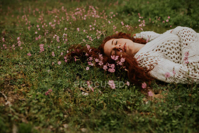 Dreamy girl lying on ground with blooming pink petals — Stock Photo