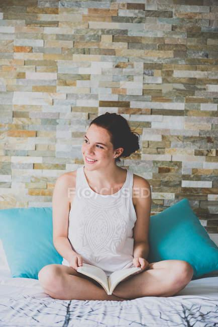 Menina sentada na cama e livro de leitura — Fotografia de Stock