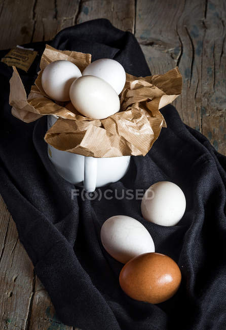 Arrangement of chicken eggs and mug on rural fabric — Stock Photo