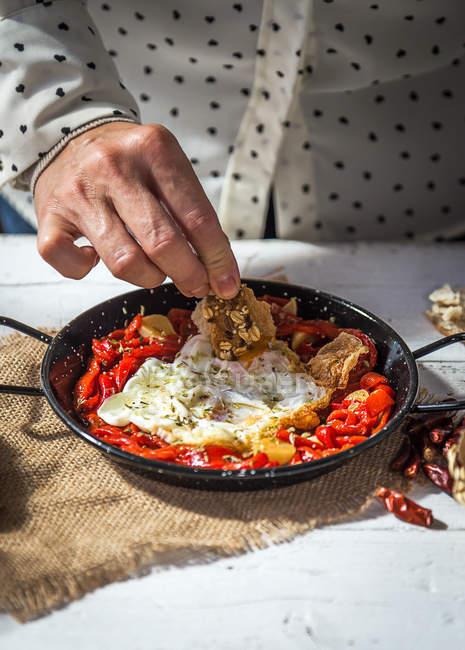 Bouchent la vue de main mettre l'ingrédient dans la poêle avec des oeufs brouillés et tomates séchées — Photo de stock