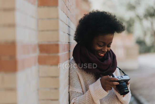 Seitenansicht eines lächelnden Mädchens, das sich an eine Ziegelwand lehnt und mit den Händen in die Kamera schaut — Stockfoto
