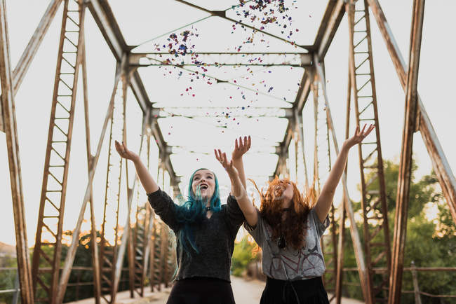 Happy girls throwing up confetti in air. — Stock Photo