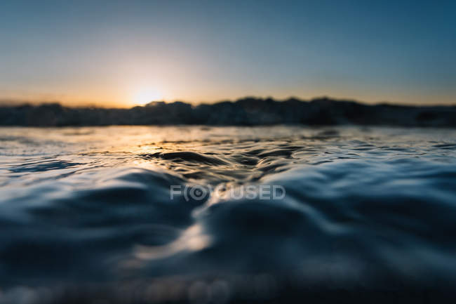 Blue water of sea wave on background of sunset. — Stockfoto