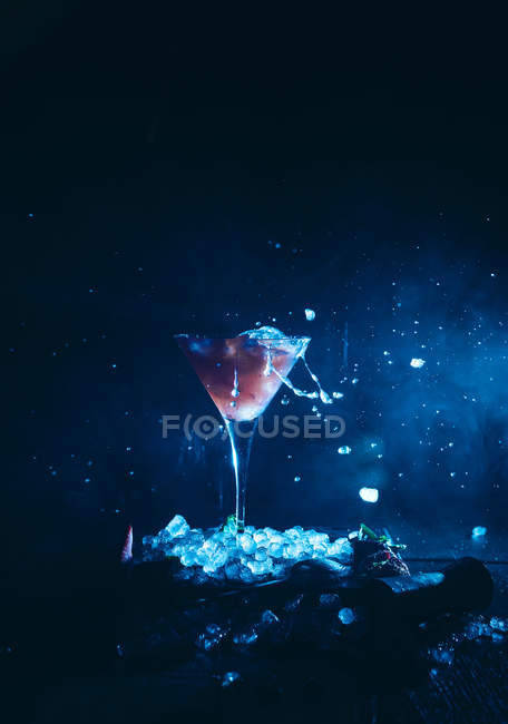 Splasing cocktail glass on ice cubes — Stock Photo