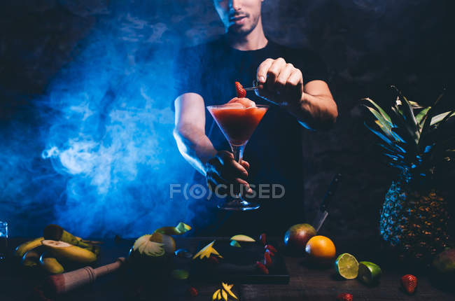 Man preparing cocktail with strawberry — Stock Photo