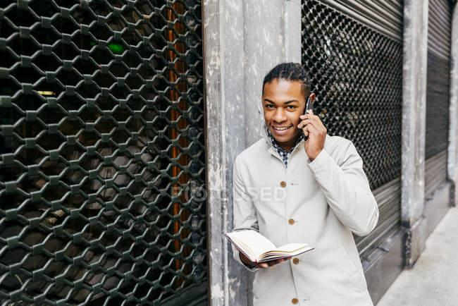 Человек смотрит ноутбука и говоря смартфон на улице — стоковое фото
