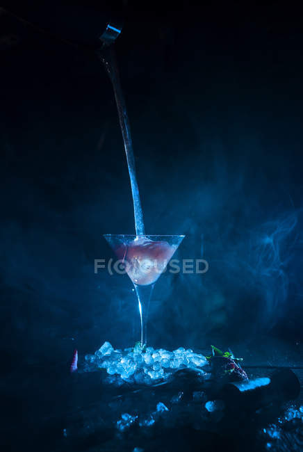 Cocktail glass on ice cubes while pouring — Stock Photo