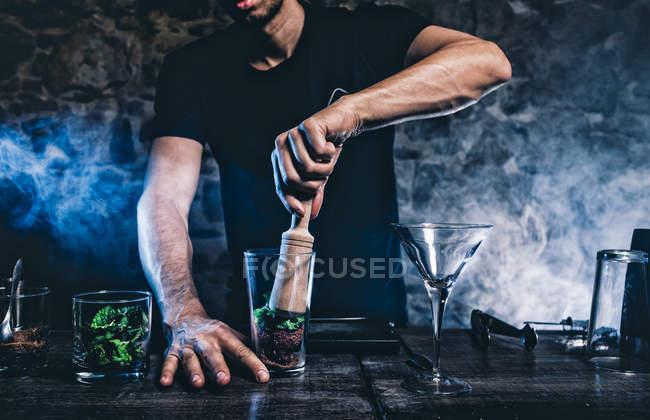 Man smashing ingridients for cocktail — Stock Photo