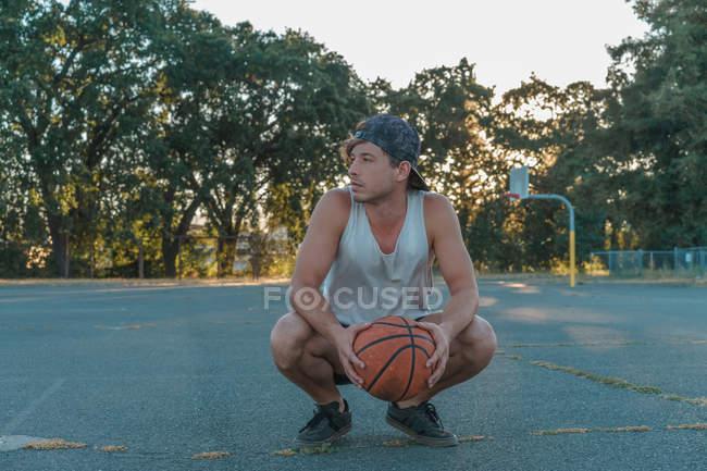 Человек в кепке приседает и держит мяч — стоковое фото