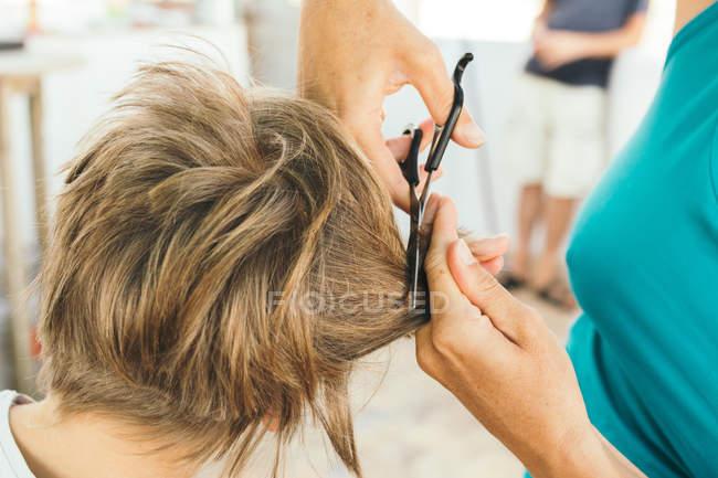 Coltiva le mani della madre tagliando i capelli del figlio con le forbici — Foto stock