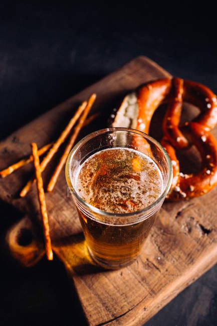Келих пива з деякими закуска як кренделі — стокове фото