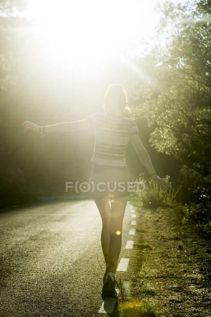 Girl walking on sunny road — Stock Photo