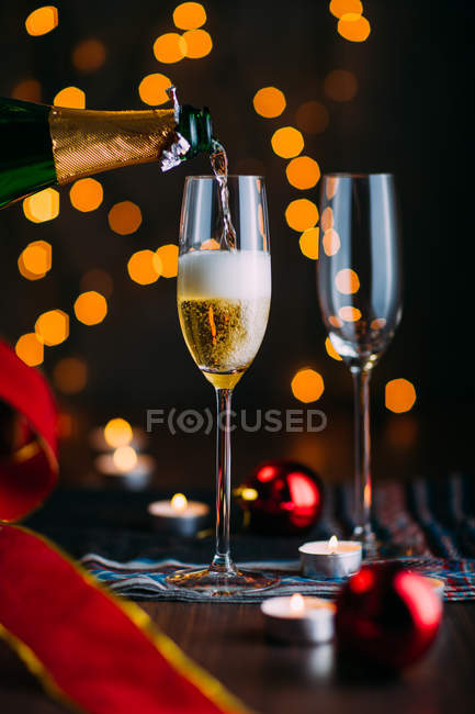 Bottle pouring champagne in glasses — Stock Photo