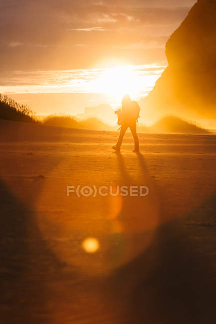 Silhouette of person walking in scenic sunset light — Stock Photo