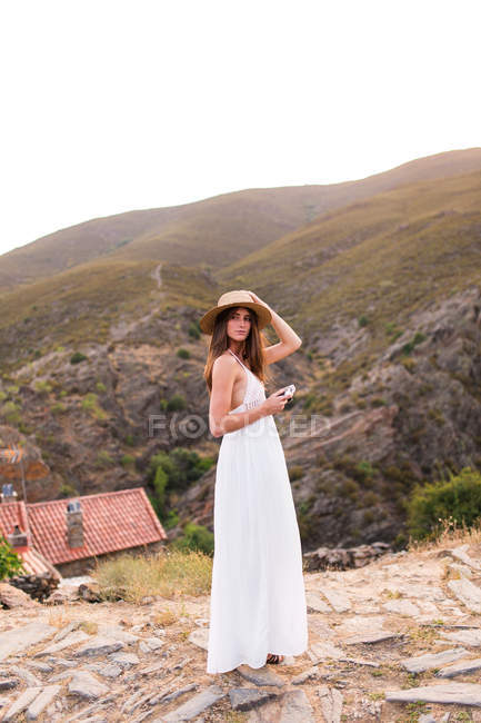 Woman with camera posing over hill — Stock Photo